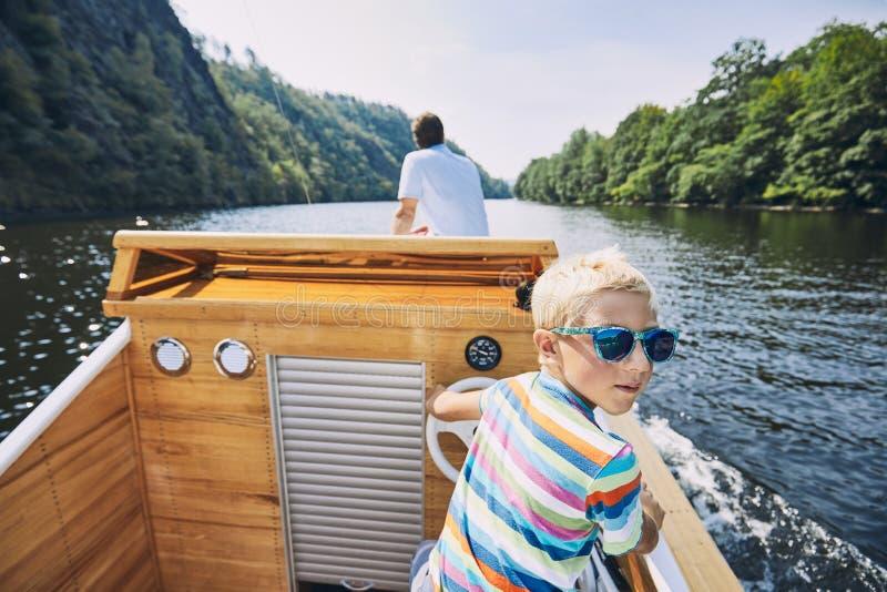 男孩主驱动电动机小船 免版税库存图片