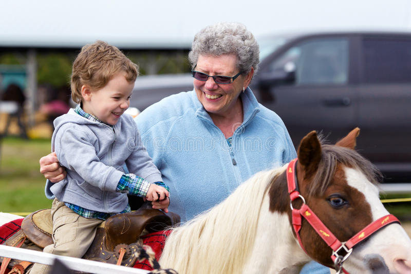 男孩乘坐小马在市场 免版税库存图片