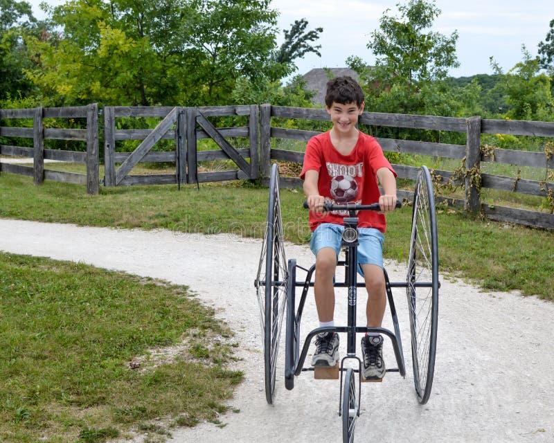 男孩乘坐的古板三被转动的自行车 库存图片