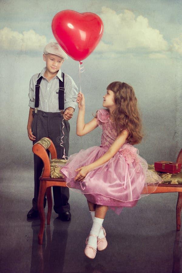男孩产生一个气球女孩 免版税库存图片
