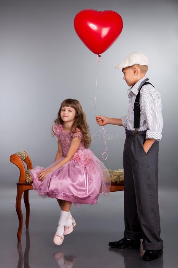 男孩产生一个红色气球女孩 库存照片