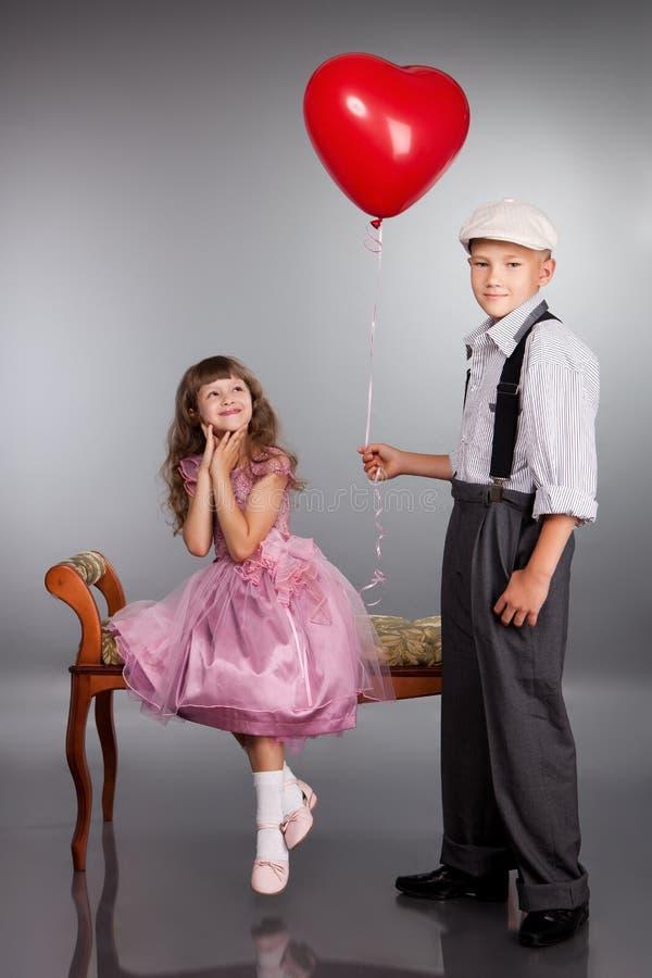男孩产生一个红色气球女孩 库存图片