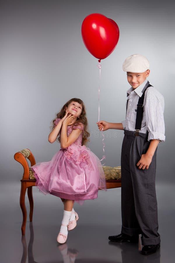 男孩产生一个红色气球女孩 图库摄影