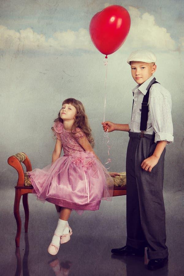 男孩产生一个红色气球女孩 免版税库存照片