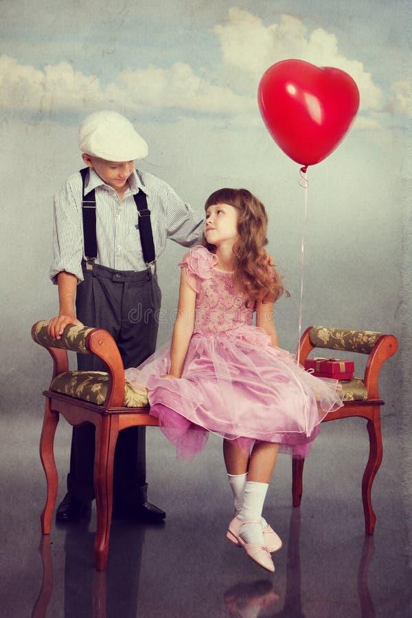 男孩产生一个红色气球女孩 免版税库存图片