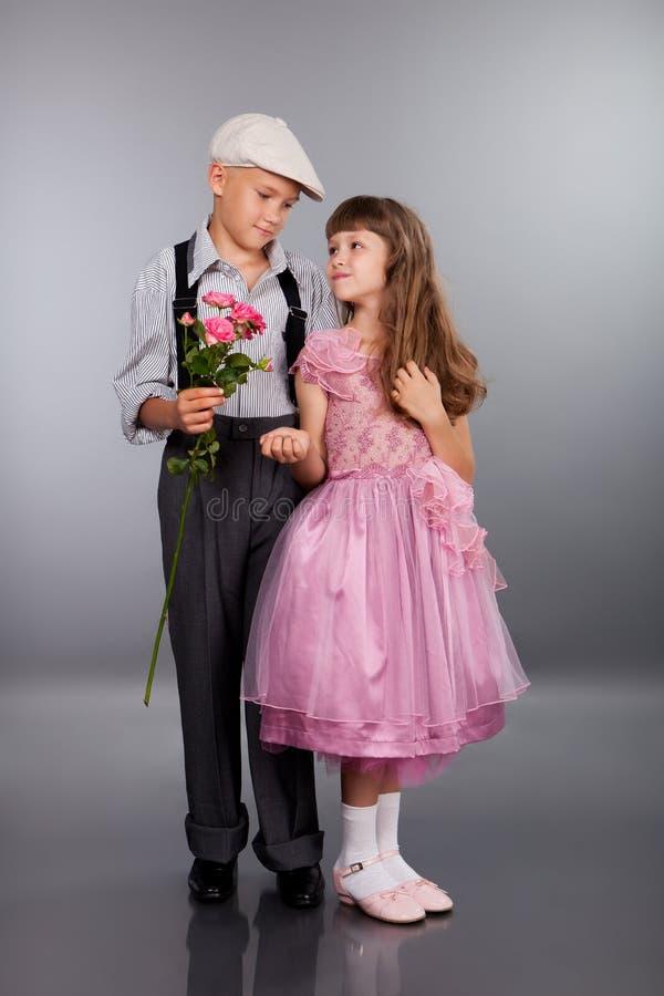 男孩产生一朵花女孩 图库摄影