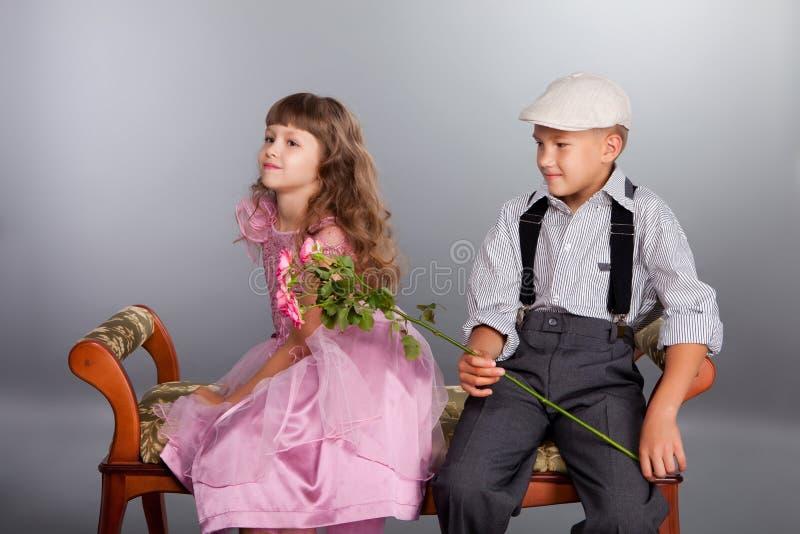 男孩产生一朵花女孩 免版税库存照片