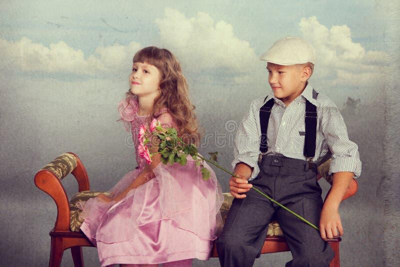 男孩产生一朵花女孩 库存照片