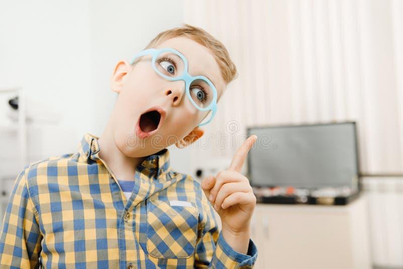 男孩产生想法的孩子,手指指向视域的玻璃在眼睛前面 库存照片