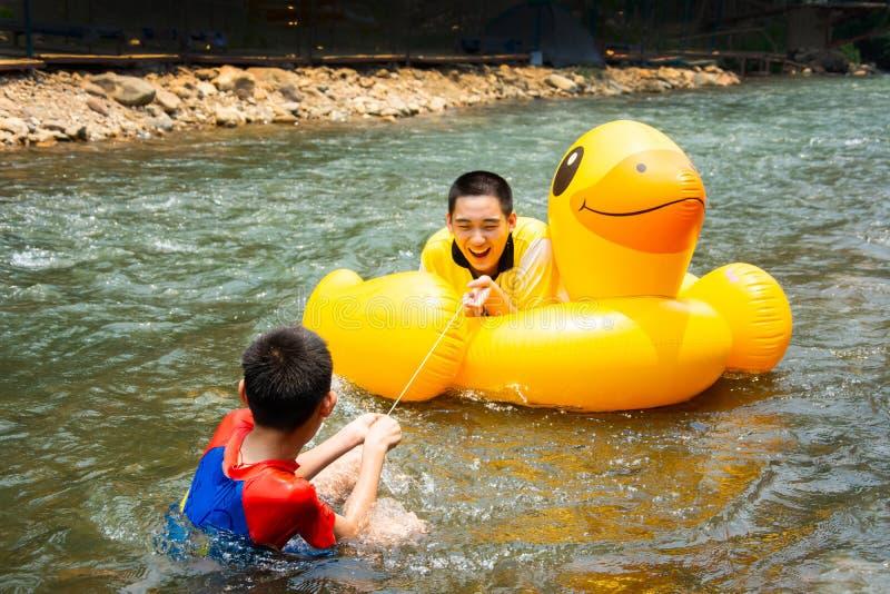 男孩享受并且获得顺流荡桨的乐趣 免版税库存图片
