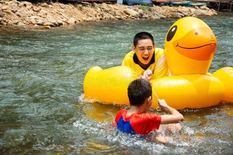 男孩享受并且获得顺流荡桨的乐趣 图库摄影