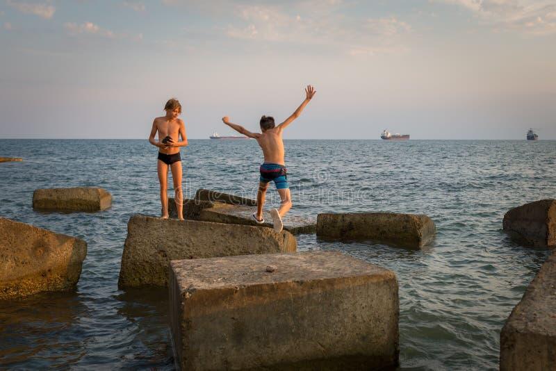 男孩从一个具体块跳到另一个在海滩 免版税库存图片