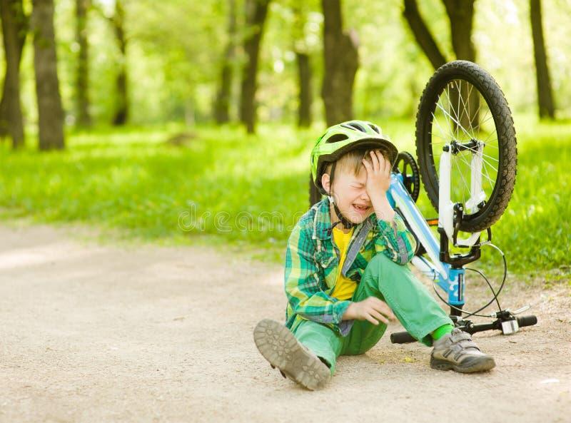 男孩从自行车跌倒了在公园 免版税库存图片