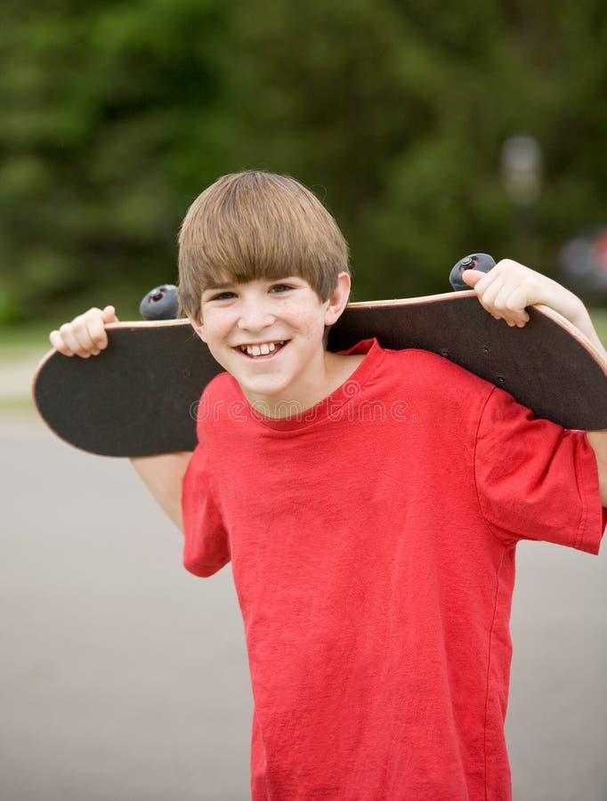 男孩他的藏品滑板 免版税库存图片