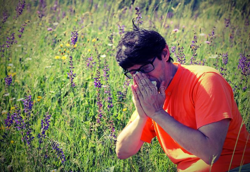 男孩以橙色衬衣喷嚏,因为过敏 库存图片