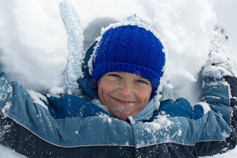 男孩位于的雪 免版税库存图片