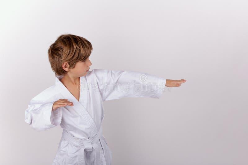 年轻男孩佩带的白色和服实践的空手道 库存图片