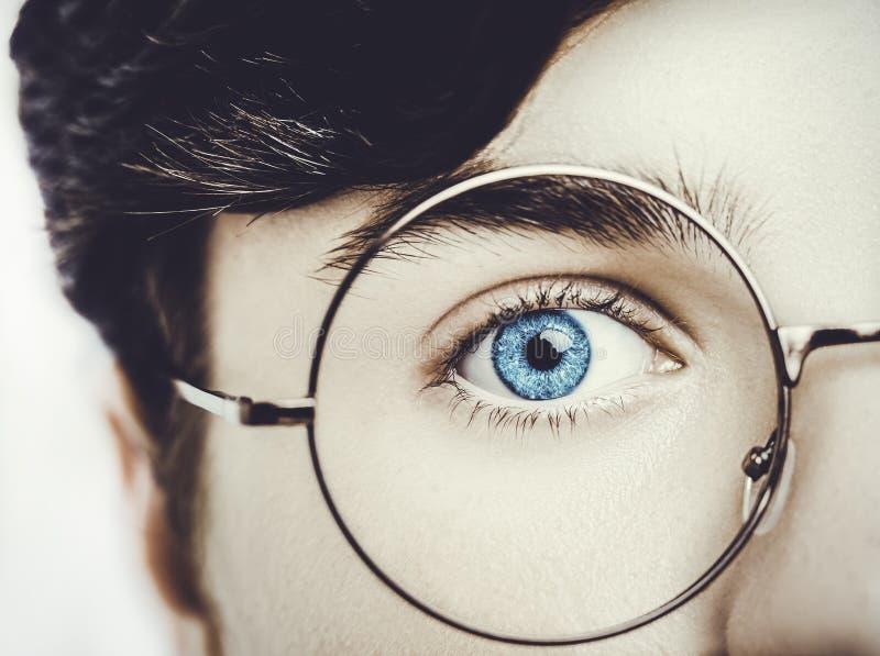 男孩佩带的镜片蓝眼睛的画象紧密,宏观演播室射击 库存照片