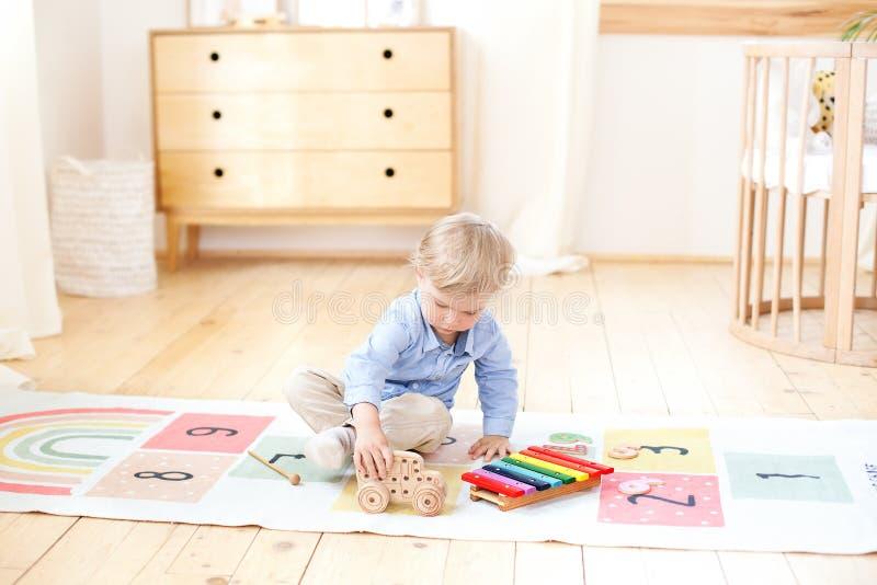 男孩使用与一台木打字机 孩子的教育木玩具 男孩的画象坐在孩子的地板 免版税库存照片