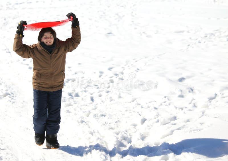 男孩使用与sledging在白色雪的冬天 库存图片