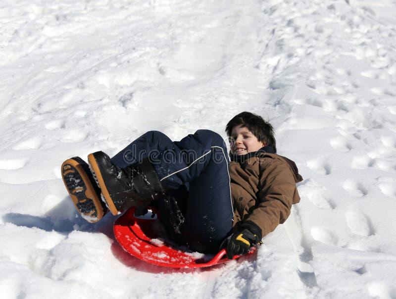 男孩使用与sledging在白色雪的冬天 库存照片