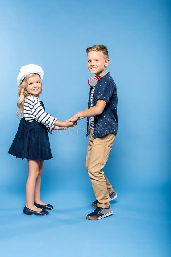 男孩侧视图有举行手和跳舞的耳机和美丽的小女孩的 免版税库存照片
