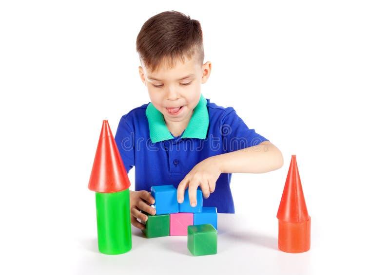 男孩修建立方体房子  免版税库存照片