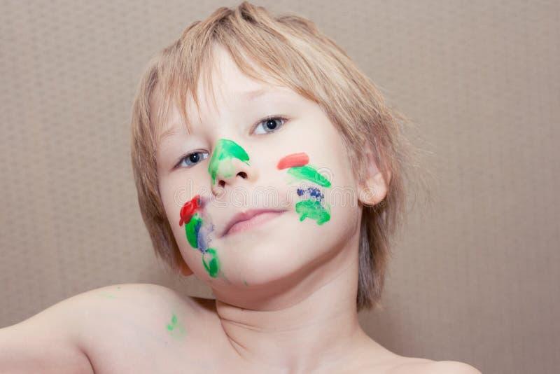 年轻男孩做与在五颜六色的油漆盖的面孔的selfie 免版税库存图片