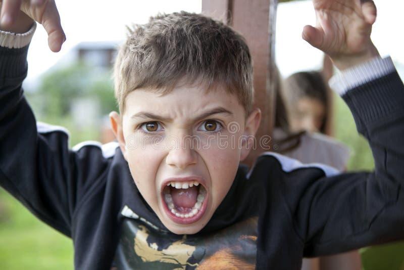 年轻男孩做面孔,并且打手势用手,好象他去 免版税图库摄影