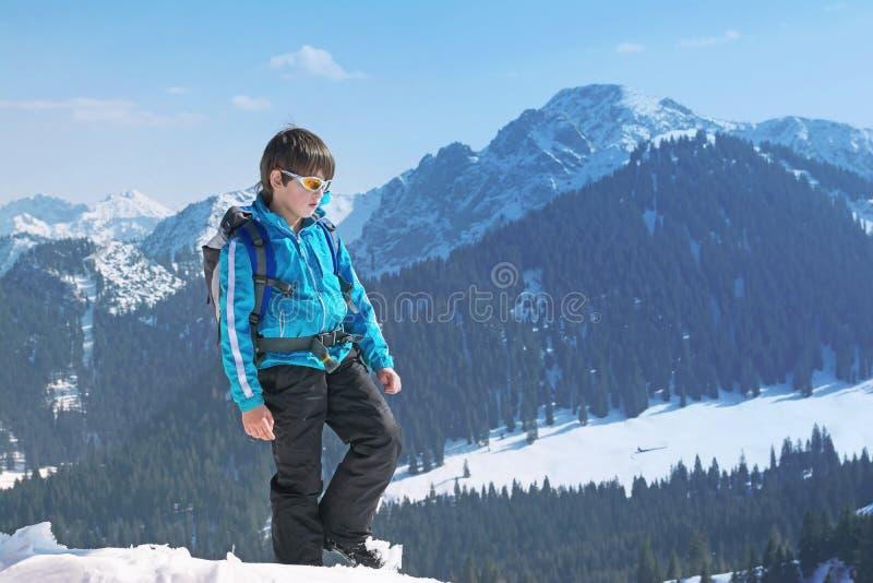 男孩儿童冬天山顶面上升 库存图片