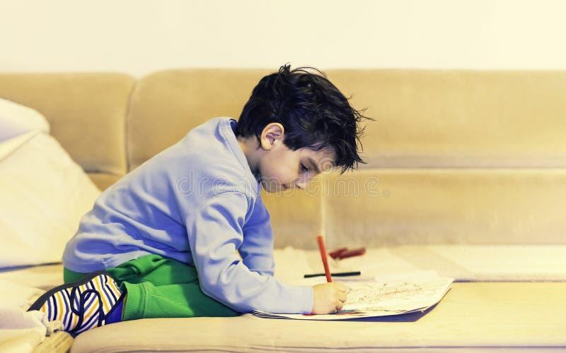 男孩儿童小小孩绘的着色和画与蜡笔,当在家坐沙发或床在享受时间的屋子里在时 免版税库存照片