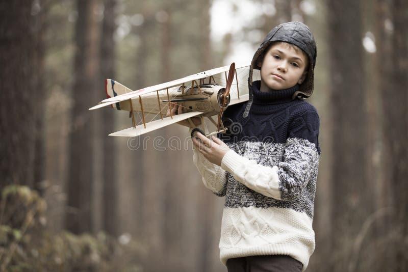 男孩充当有玩具飞机的森林 在w的秋天比赛 库存照片