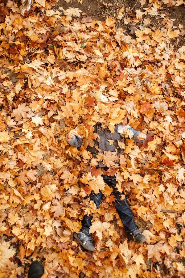 男孩充当秋天公园 开掘入落叶 免版税库存图片