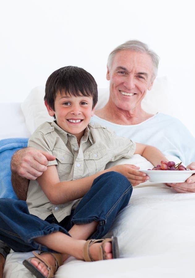 男孩关心逗人喜爱的祖父采取他的一&# 图库摄影
