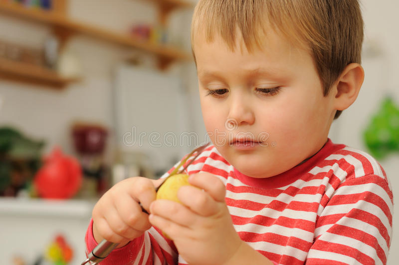 男孩削皮土豆年轻人 库存图片