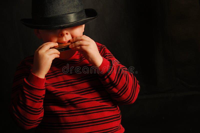 男孩口琴 免版税库存图片