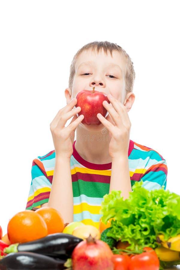 男孩吃一个红色水多的苹果,在白色的画象 免版税库存图片