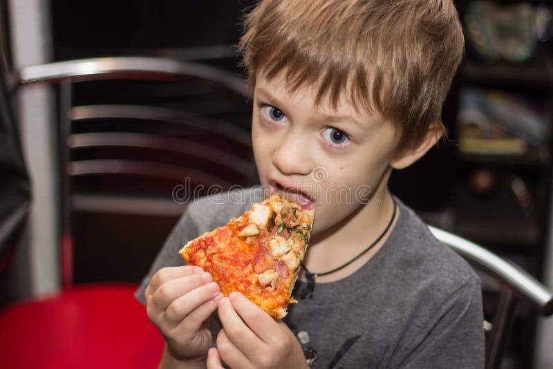 男孩吃一非常鲜美比萨高兴地巨大 免版税库存图片
