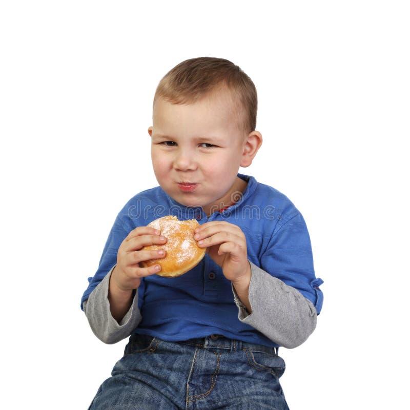 男孩吃小圆面包 免版税库存照片