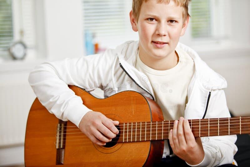 男孩吉他使用少年 库存图片