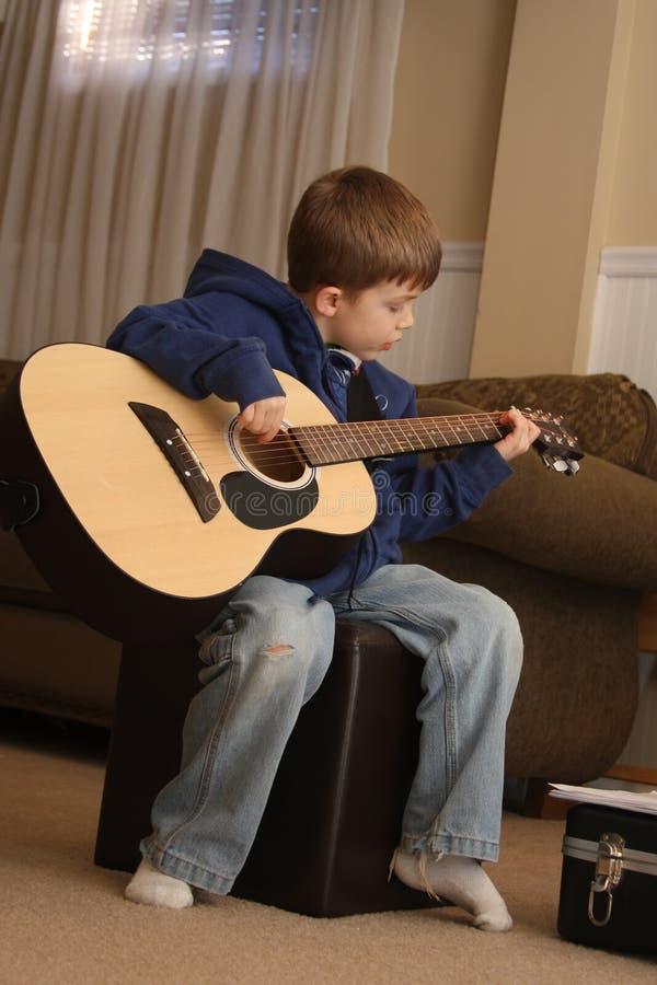 男孩吉他使用 库存图片