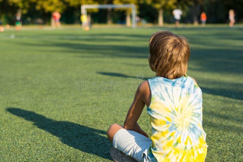 男孩后面坐草在的体育场的边缘 免版税图库摄影