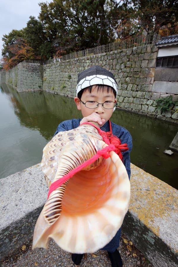 男孩吹蜗牛喇叭 图库摄影