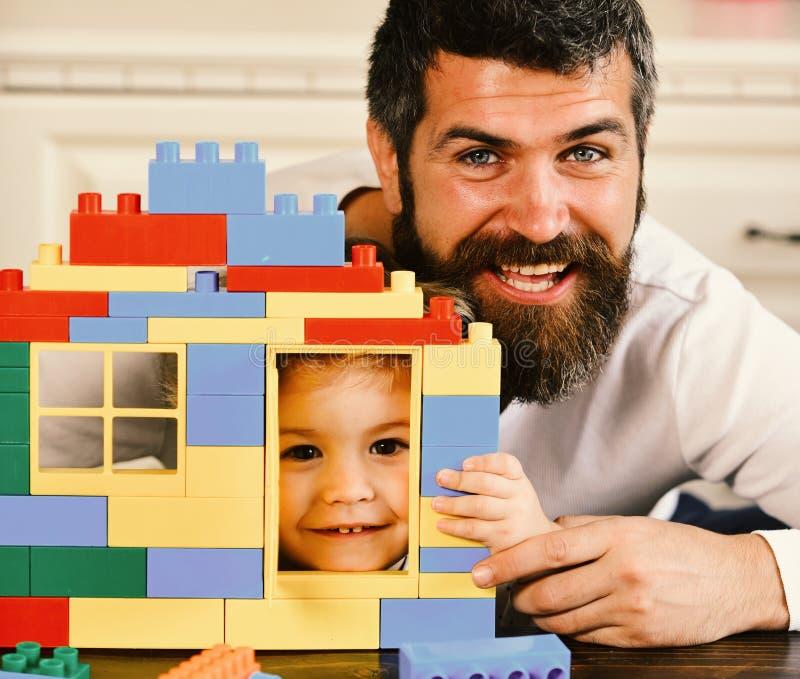 男孩和人defocused背景的 父亲和儿子有微笑的面孔的拿着玩具砖建筑 免版税库存图片