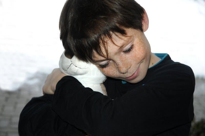 男孩和他喜爱的stuffede动物 免版税库存图片