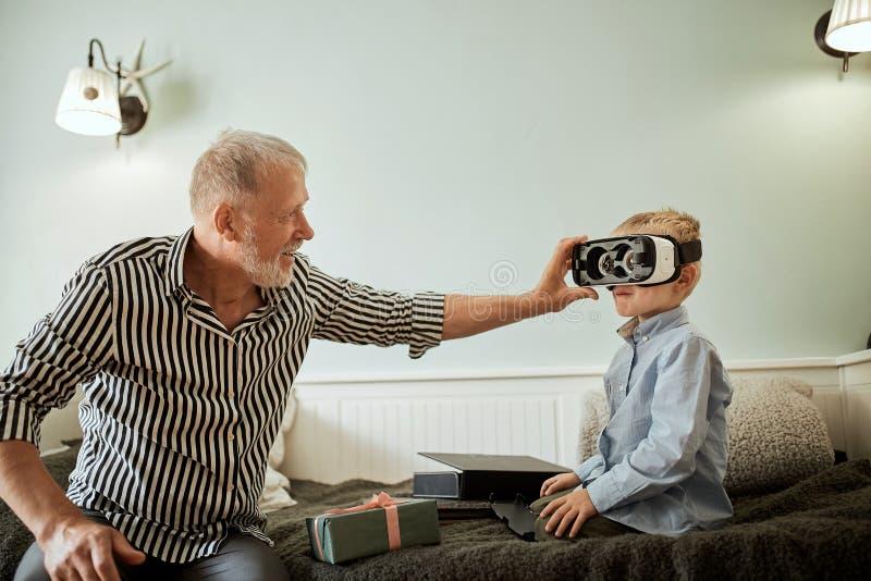 男孩和他的在家使用在沙发的祖父vr玻璃 免版税库存图片