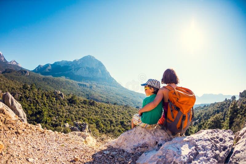 男孩和他的母亲坐山的上面 免版税库存照片