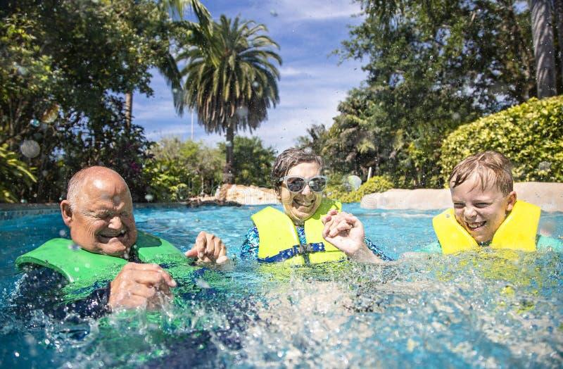 男孩和他的祖父母飞溅,演奏和获得乐趣在水公园 免版税图库摄影