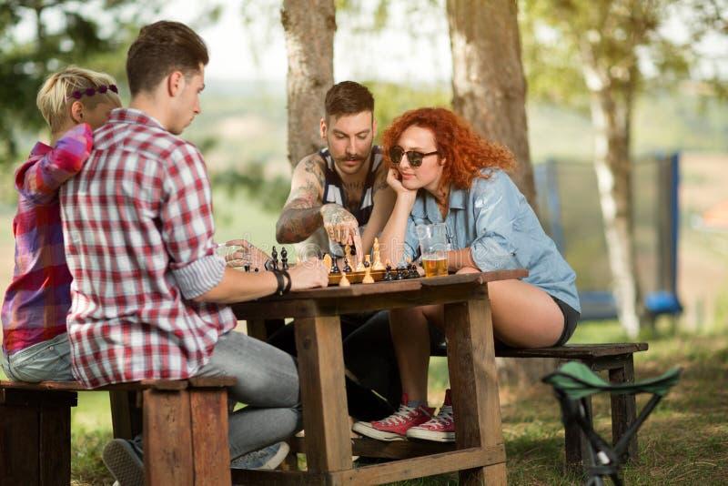 男孩和女孩使下棋快乐 免版税图库摄影