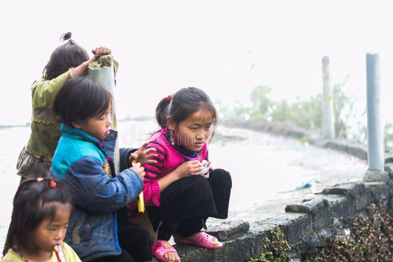 男孩和女孩使用在街道附近的外套的在猫猫村庄 库存图片